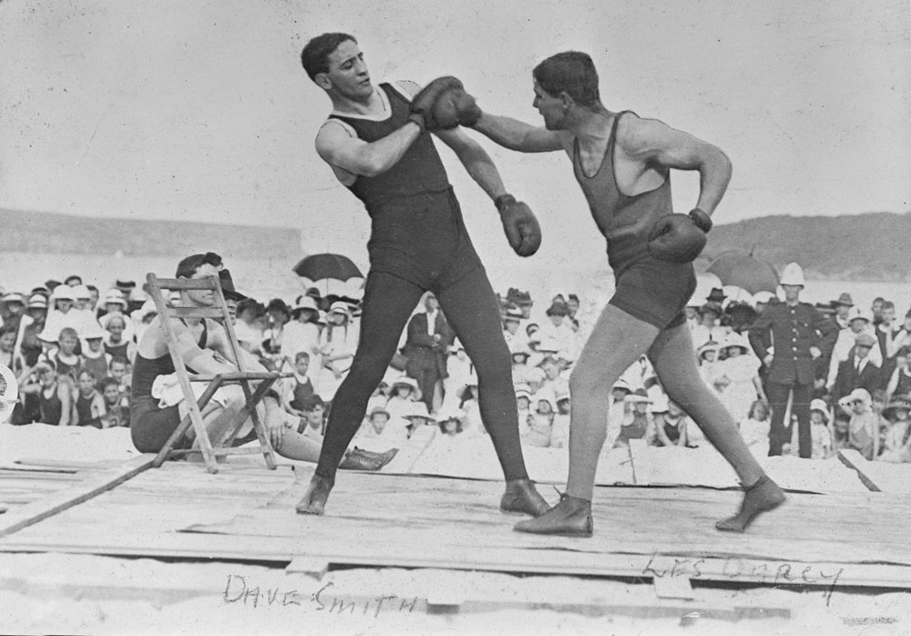 Les Darcy's parents migrated from Ireland. Here he is shown (on right) sparring with his trainer at the beach, watched by his admirers. (NAA:  A1200, L24688)