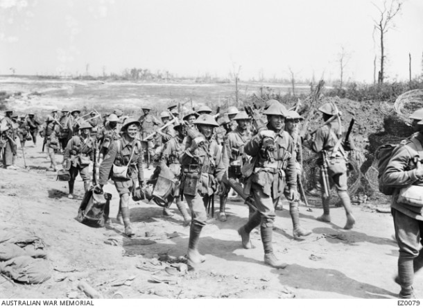 Australian machine gunners returning from the front line trenches to their billets. The Australian machine gunners have been identified as members of either the 5th, 6th or 7th Machine Gun Companies, 2nd Australian Division, and are probably walking along a road near Pozieres. Each of the two men at the front of the group is carrying a Vickers Mark I machine gun. The identifications of these two men might possibly be 701 Kenneth Mackenzie of Bundaberg, Qld, and 792 Alfred Bernard Charles Anderson, of Brisbane, Qld, both of the 7th Machine Gun Company. Some men carrying picks are heading in the opposite direction. Courtesy AWM, ID EZ0079