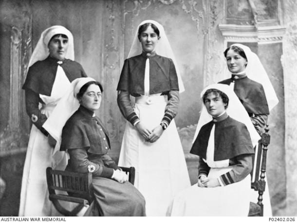Studio portrait of five sisters of the AANS stationed at No. 1 Australian Auxiliary Hospital and wearing the 1914 working dress. Seated in the front row on the left is Matron Ethel Gray, whose rank is shown by her thick brown cuffs and stand collar.