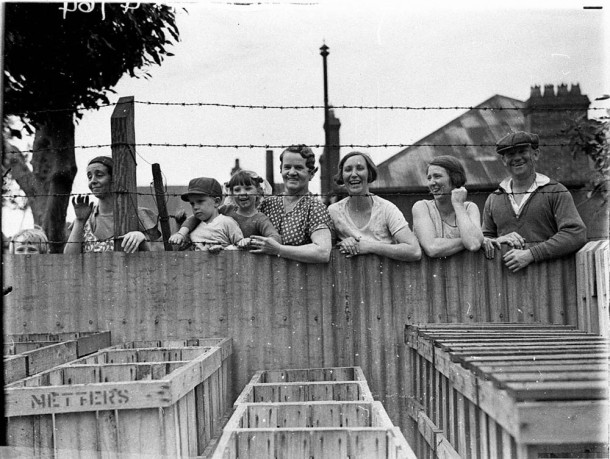 Crowds peer over a fence, c.1934. Photographed by Sam Hood. Courtesy State Library NSW, ID DG ON4/4764.
