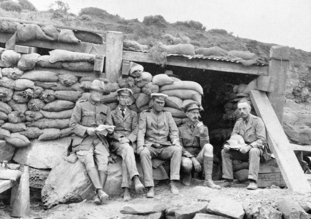 Three RANBT officers pictured outside the sandbagged dugout that acted as the Wardroom at Kangaroo Beach, Suvla Bay. Courtesy AWM, ID P11155.007.001.