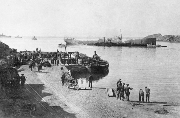 West Beach, Suvla, Gallipoli. The 1st Royal Australian Naval Bridging Train is here placing an old hulk in position to act as an outer breakwater for the boat docks. Although organised along army lines, the RANBT's members were proud to retain naval ranks and ratings. They wore khaki uniform, complete with slouch hat, but replaced the AIF's rising sun badge with a fouled anchor insignia. Courtesy AWM, ID P01326_008.