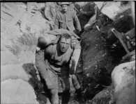 A still from the 1916 film The Battle of the Somme showing the wounded man and his mysterious rescuer. Courtesy Imperial War Museums.
