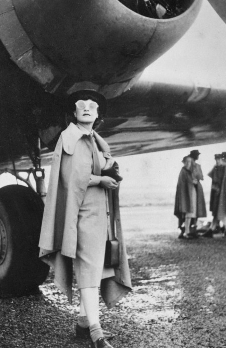 Journalist Iris Dexter standing beneath the starboard engine of an aircraft during the Women War Correspondents' Tour, 1943, photographed by  Barbara Joan Isaacson. Courtesy AWM, ID P05161.017.